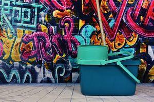 Ein Wischeimer vor einer Wand mit Grafitti